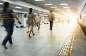 foto of commutator  - Motion blurred commuters walking in subway station - JPG