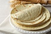 picture of whole-wheat  - Stack of homemade whole wheat flour tortilla on napkin - JPG