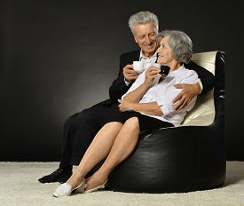 stock photo of debauchery  - Portrait of a senior couple with cap of coffee over a black background - JPG