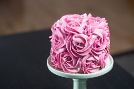 picture of icing  - Gourmet cake for a wedding or birthday decorated with pink icing sugar roses covering the surface displayed on a stand over a black background with copyspace - JPG