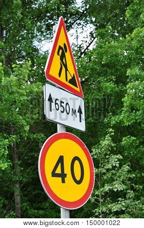 road signs speed limit and a repair the road