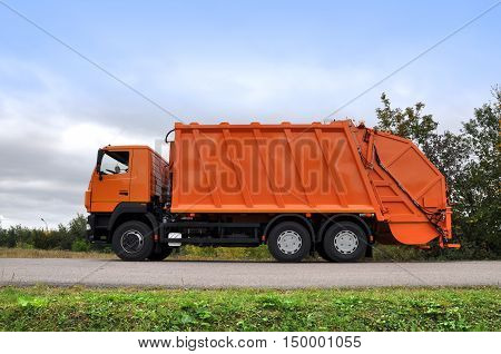 Orange new refuse collection vehicle on the road. Side view.