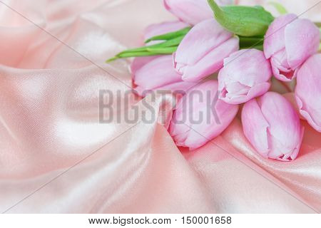 Bouquet of tulip flowers on a background of silk fabric; with copy-space