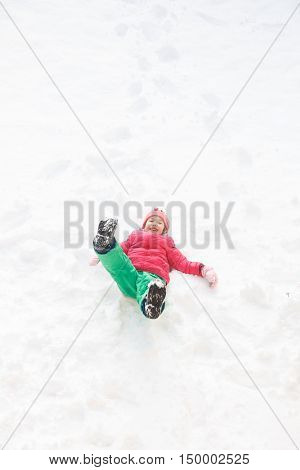 Playful girl with braids playing in snow jumping and diving in it having fun and being active. Natural lifestyle and free childhood concept with copy space.