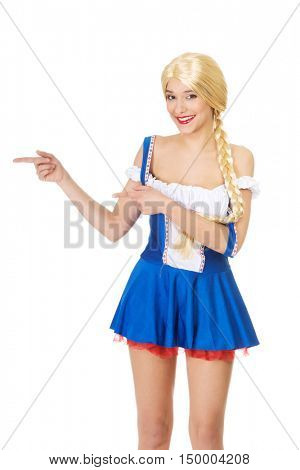 Woman in Bavarian dress pointing aside.