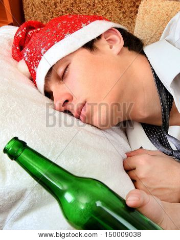 Young Man sleep in Santa Hat with Bottle of the Beer on the Sofa closeup