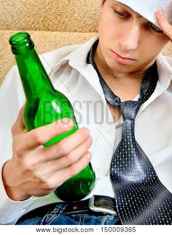 Sad and Tired Young Man with Bottle of the Beer