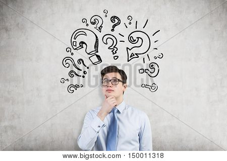Young businessman attacked by aggressive question mark images on concrete wall. Concept of too many questions. Mock up