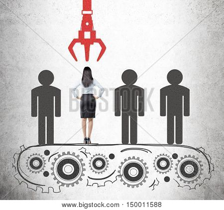 Portrait of businesswoman standing with her back to the viewer on conveyor belt and being picked up unlike her competitors. Concept of HR work