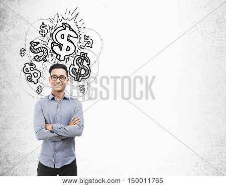 Asian businessman with glasses standing near concrete wall with shining dollar signs on it. Concept of making big bucks. Mock up