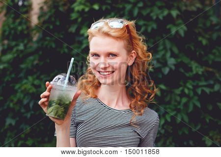 Smiling ginger woman in sunglasses with cocktail in hand at green bush, photo toned