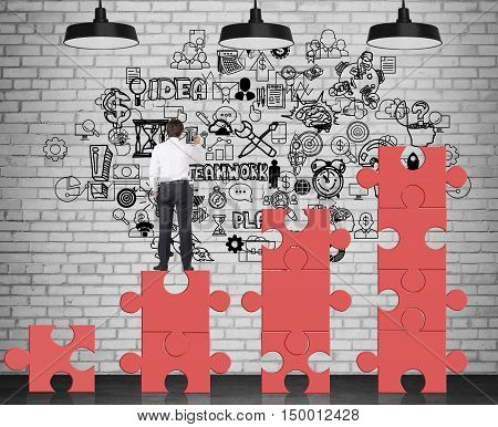 Rear view of businessman standing on red puzzle pieces and drawing business sketch on brick wall. Concept of management