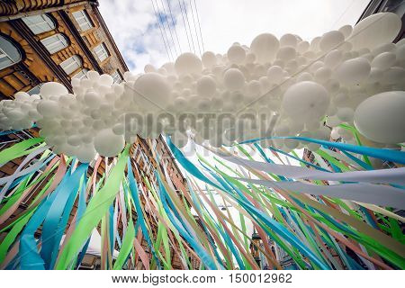 lot of white balloons fastened together into one and colorful long ribbons at the festival