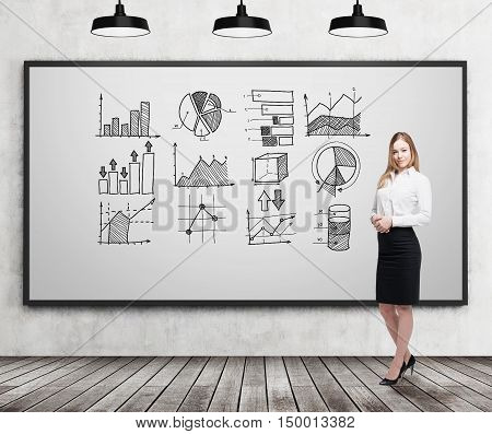 Smiling blond businesswoman standing near whiteboard with graphs on it. Concept of statistics in business.