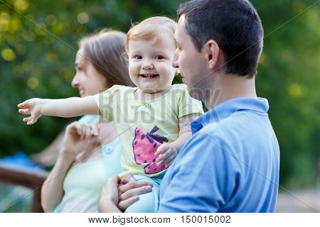 Happy family with little daughter on bridge in summer park