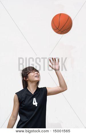 Asian basketball player look up at ball