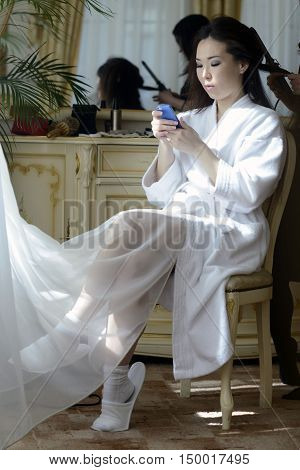 Beautiful Bride In White Dressing Gown Is Holding Phone In Her Hands. Beauty Model Girl In Wedding R
