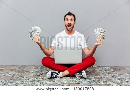 Happy excited casual man sitting on the floor with laptop and holding money over gray background