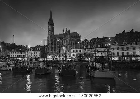 Port, houses, restaurants, shops, bars, pubs and Cathedral at night in Cobh, Ireland. Famous tourist seaport town and popular touristic destination. Black and white