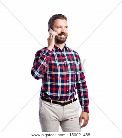 Young handsome hipster man in checked red shirt, holding smart phone, making phone call, studio shot on white background, isolated