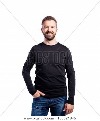 Young handsome hipster man in black long-sleeved t-shirt, hand in pocket, studio shot on white background, isolated