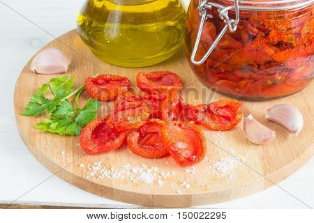 homemade sun-dried tomatoes with a jar of tomatoes on wooden desk