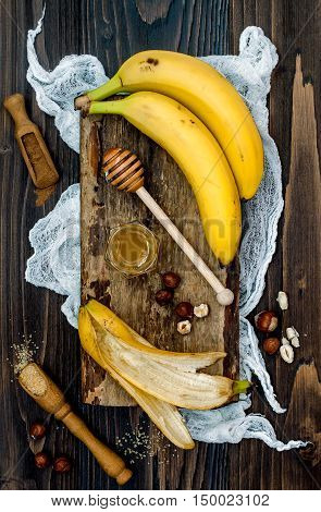 Preparing healthy fall and winter breakfast bowl. Caramelized bananas honey dipper and hazelnuts over wooden board. Overhead top view flat lay. Rustic country style. Ideal Christmas morning meal concept