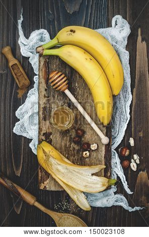 Preparing healthy fall and winter breakfast bowl. Caramelized bananas honey dipper and hazelnuts over wooden board. Overhead top view flat lay. Rustic country style. Ideal Christmas morning meal concept. Toned image