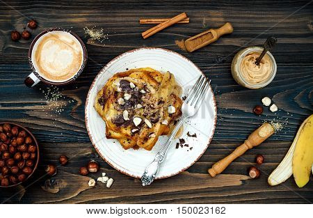 Preparing healthy fall and winter breakfast. Vegan vanilla french toast with caramelized bananas raw dark chocolate and hazelnut butter. Overhead top view flat lay. Rustic country style. Ideal Christmas morning meal concept