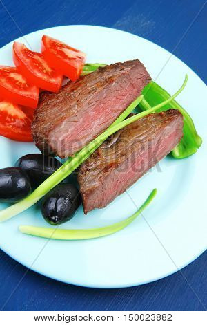 meat food : roast beef fillet mignon served on blue plate with chili pepper and tomatoes over blue wooden table