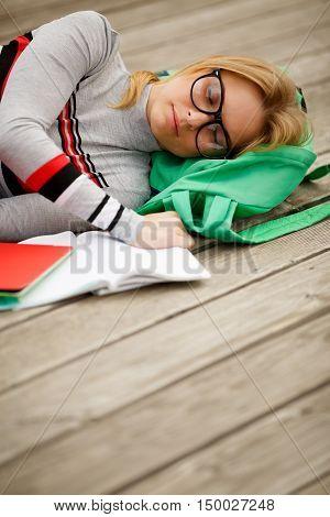 sleeping studenka with open notebook on wooden floor in summer