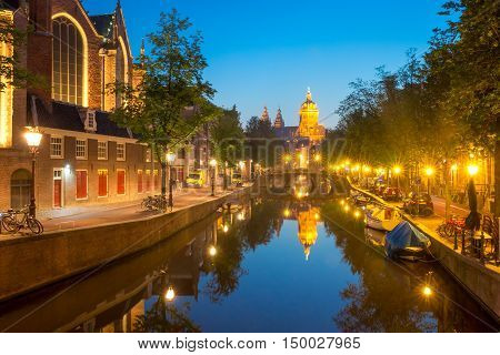 Night red-light district De Wallen, canal, bridge, Basilica of Saint Nicholas and its mirror reflection, Amsterdam, Holland, Netherlands. Long exposure.