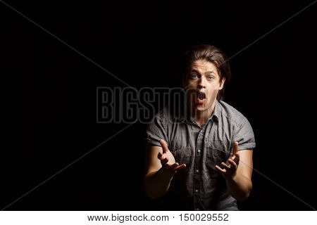 Dissapointed young handsome man gesturing, shouting over black background. Copy space.
