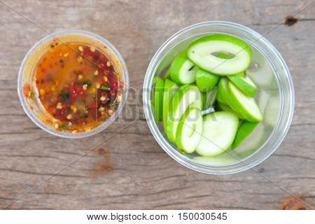 Fresh sweet and sour green sliced mango with chili paste for tropical fruit top view