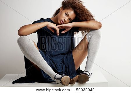 Black Woman Sits On The Tanle Wears Dress And High-knee Socks