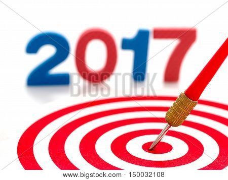 2017 year goal red bullseye dart arrow hitting target center dartboard and blur two thousand seventeen in background. Happy New Year.