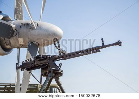 Retro gun on the tripod and optical sight, against the backdrop of the aircraft propellers, close-up. Machine gun outdoors.