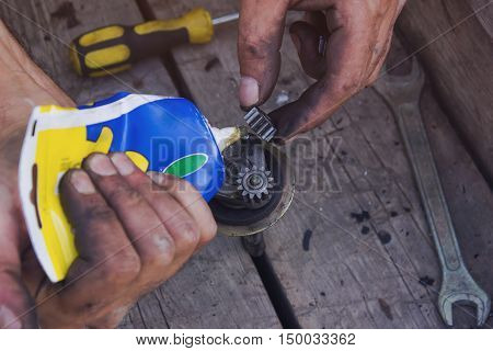 The mechanic lubricates the parts from the gear of the starter from the car