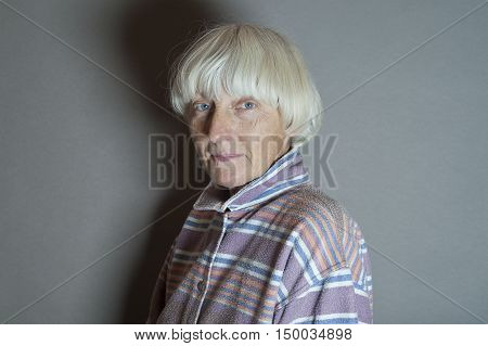 Woman with short gray hair looking happily cropped studio portrait