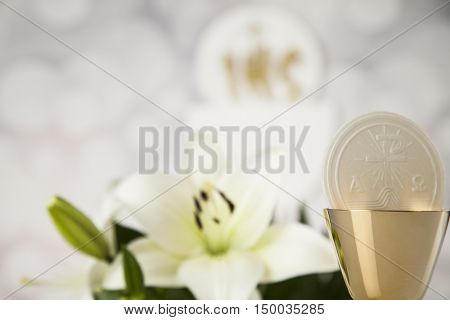 Holy communion a golden chalice with grapes and bread wafers