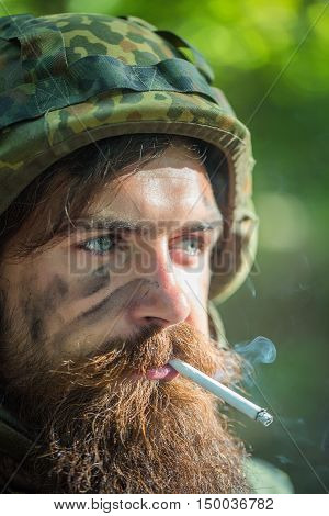 Soldier man with tied and grime bearded face in military helmet and ammunition smoking cigarette outdoor closeup