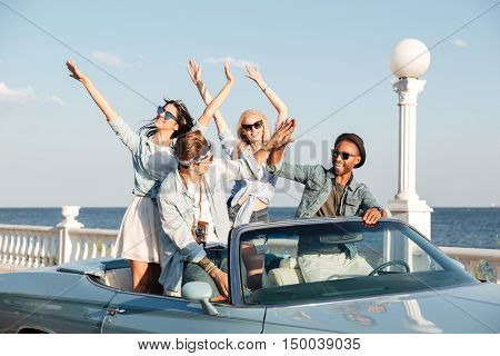 Group of cheerful young people giving high five and having fun in car cabriolet