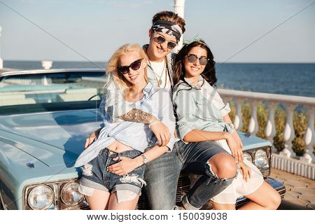 Happy young man and two attractive women standing together near vintage cabriolet