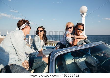 Multiethnic group of happy young people talking and having fun in cabriolet