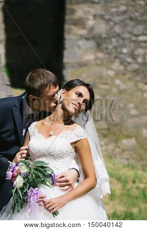 Handsome groom man holds and kisses beautiful bride woman outdoors on sunny day on masonry wall