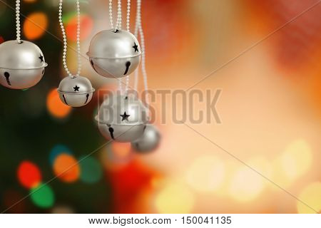 Jingle bells on blurred Christmas lights background, closeup