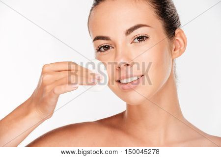 Skin care woman removing face makeup with cotton swab pad isolated on a white background