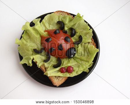 The ladybug is made of tomato and olives. Ridiculous food for good mood. The ladybug is located on a lettuce leaf bread.