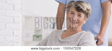 Close shot of smiled woman on a wheelchair with her caregiver standing behind