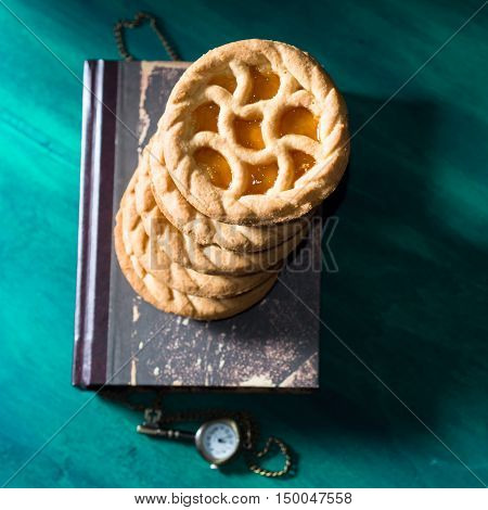 Shortcrust tartlets with peach jam stacked on a book on dark green and black background. Square image